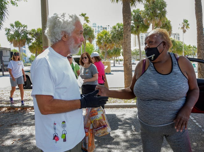 Volunteer Dan Buchler gives Queen Jones several loaves of bread after she and her two siblings get Johnson & Johnson COVID-19 vaccinations in May in the Van Wezel Performing Arts Hall parking lot. All Faiths Food Bank held a large-scale food distribution in partnership with Van Wezel. The Sarasota County Health Department and Shots in Arms gave the one-dose shots.