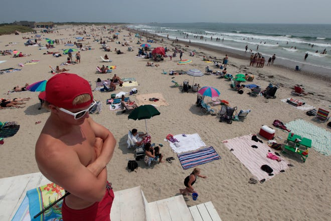 In this 2011 file photo, Owen Worden, lifeguard, keeps his eye on the above average number of people in the water.  Bathers seek shelter from the heat in the waters at Horseneck Beach in Westport.