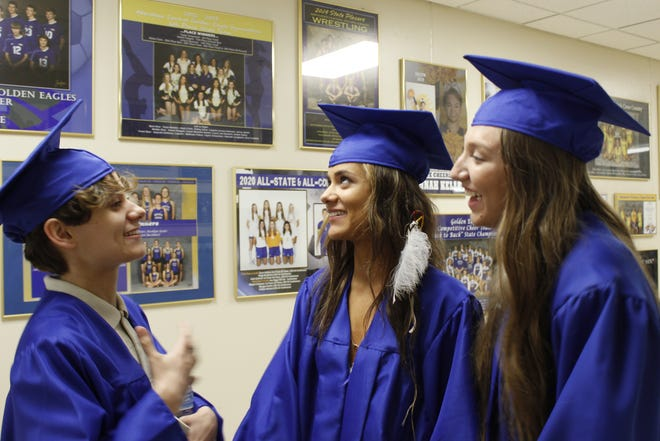 Andrew Fabert, Elycia Fabert and Madisyn Voegele visit before the Central High School graduation ceremony Sunday afternoon.