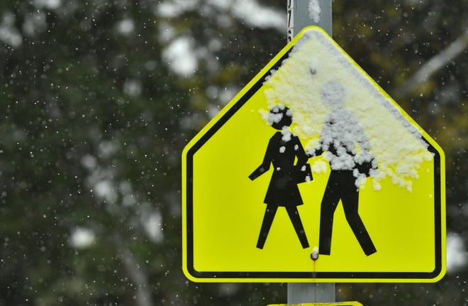 Snow falls on a school crossing sign in Kansas City in late October 2020.