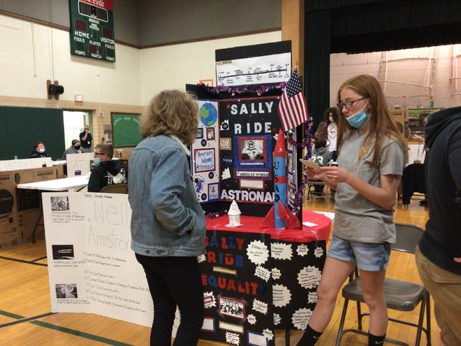 Seventh grade student Layla Overly presents her project to eighth grade student Kylee Ware.