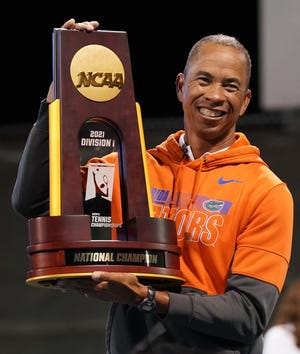 Florida coach Bryan Shelton holds up the NCAA championship trophy after the Gators defeated Baylor to win the NCAA D1 Men's Tennis Tournament on Saturday night at the USTA National Campus in Orlando.