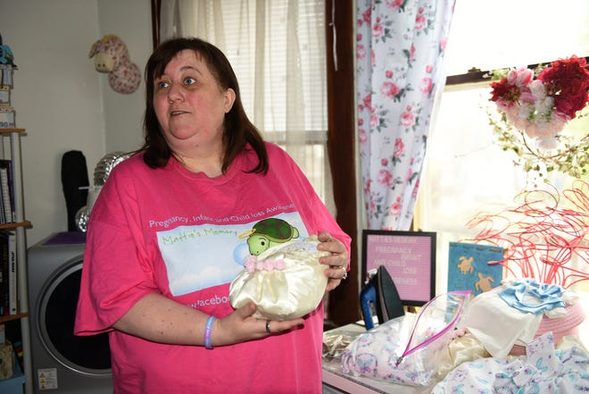 """Hazel Jones makes donation bags with burial gowns and caps for families who have lost children at her home April 27, 2021, in Milwaukee. Jones holds a bassinet she made for donation. """"I just hate to see people hurting."""""""