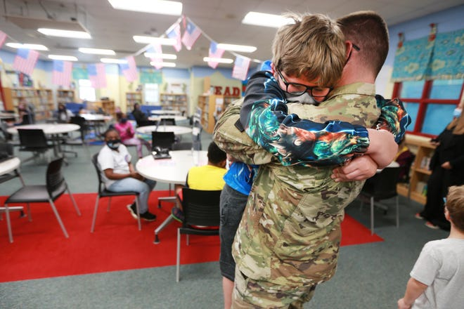 Corbin Otts, 10, a fourth grader at Lawndale Elementary School, embraces his dad, Michael Otts, a staff sergeant with the U.S Army National Guard, as he is surprised by his return home inside the media center at Lawndale Elementary School on Wednesday, May 19, 2021, in Tupelo, Miss. Otts has been on an 11 month deployment in Kuwait.