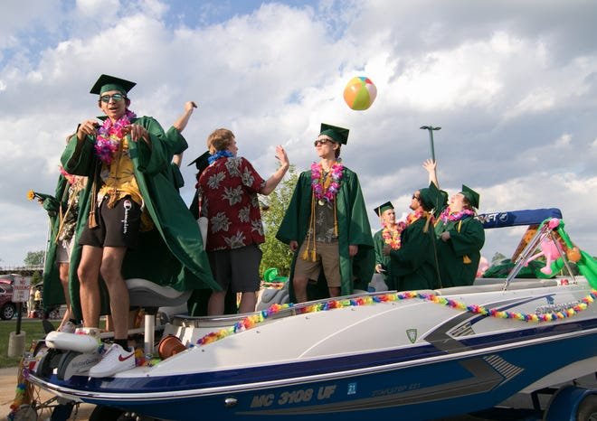 A group of Howell High School graduating seniors celebrate on their way to the informal commencement riding a trailered boat through the school's parking lot Saturday, May 22, 2021.