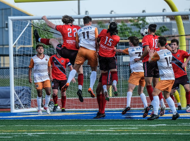 Lansing Common players Aidan O'Connor (22), Munir Sherali (15) and Omar Shady (18) successfully defend a kick against West Michigan Bearings on Saturday, May 22, 2021.