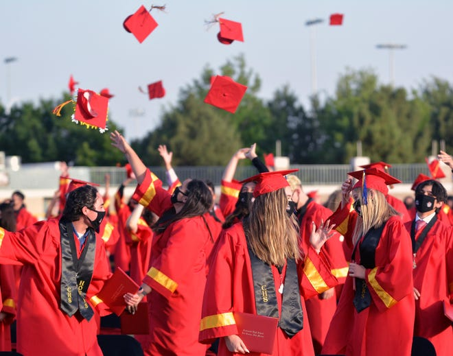 Graduates flip their mortarboards and tassels into the air during the graduation ceremony for Centennial High School at The Field of Dreams in Las Cruces on Saturday, May 22, 2021.