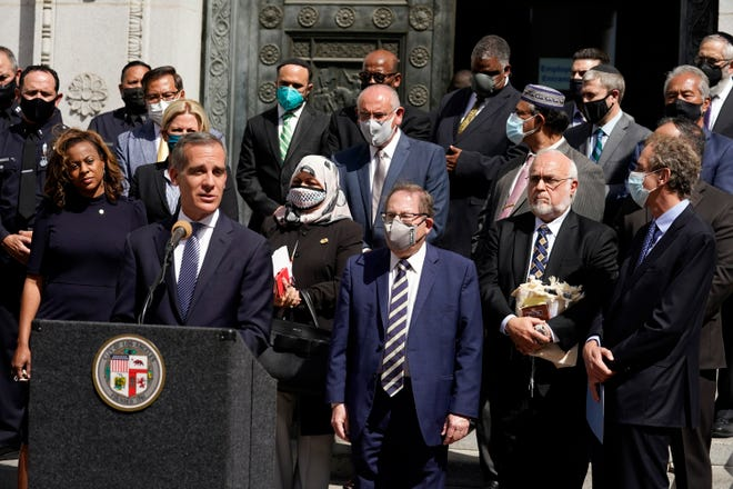 Los Angeles Mayor Eric Garcetti, at podium, speaks in front of civic and faith leaders outside City Hall in Los Angeles on May 20, 2021. Faith and community leaders in Los Angeles called for peace, tolerance and unity in the wake of violence in the city that is being investigated as potential hate crimes. Los Angeles police on Saturday announced the arrest of a suspect in an alleged attack by a pro-Palestinian group on Jewish men outside a restaurant earlier in the week.