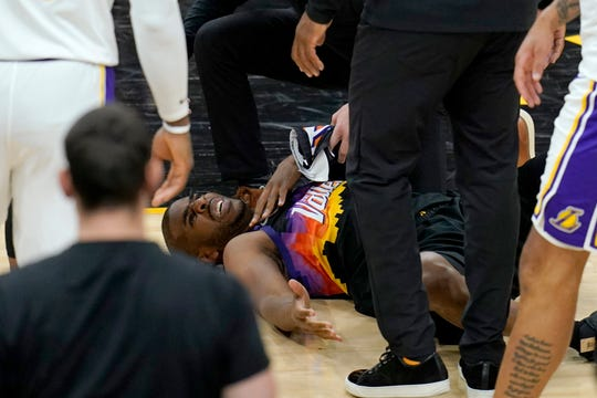 An injured Phoenix Suns guard Chris Paul grimaces in pain during the first half of Game 1 of their NBA basketball first-round playoff series against the Los Angeles Lakers Sunday, May 23, 2021, in Phoenix. (AP Photo/Ross D. Franklin).
