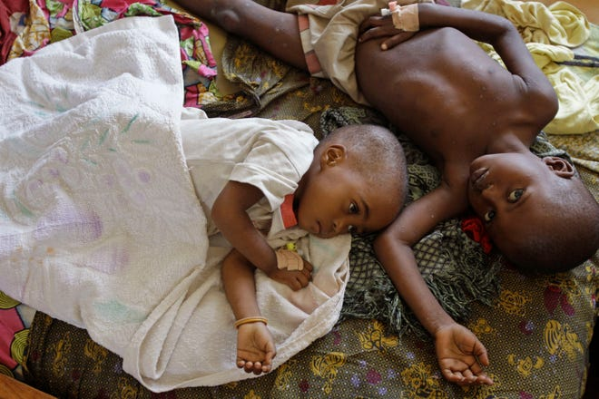 Two children stricken with malaria rest at a hospital in Walikale, Congo, on Sept. 19, 2010.