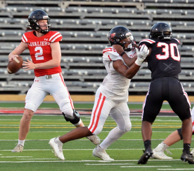 Lake Travis quarterback Bo Edmundson looks for an open receiver while running back Nico Hamilton keeps linebacker Tremain Lewis from applying pressure during the Cavaliers' spring scrimmage Friday.