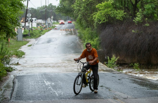 David Zurovetz stops at the low water crossing on Old Bee Cave Road, where Williamson Creek was flowing over the pavement after a series of downpours Monday.
