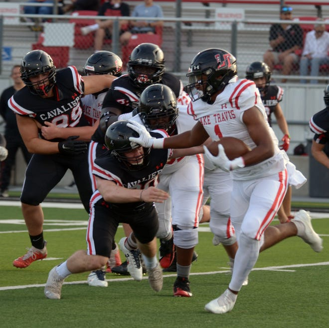 Lake Travis running back Nico Hamilton delivers a stiff-arm to defensive lineman Ezekiel King early in the Cavaliers' spring scrimmage. Hamilton will be one of a handful of backs vying for carries this season.
