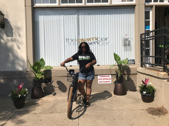 Rashauna Johnson, owner of The GLAM Bar, poses outside her business with one of the new bikes that she is offering to city visitors.
