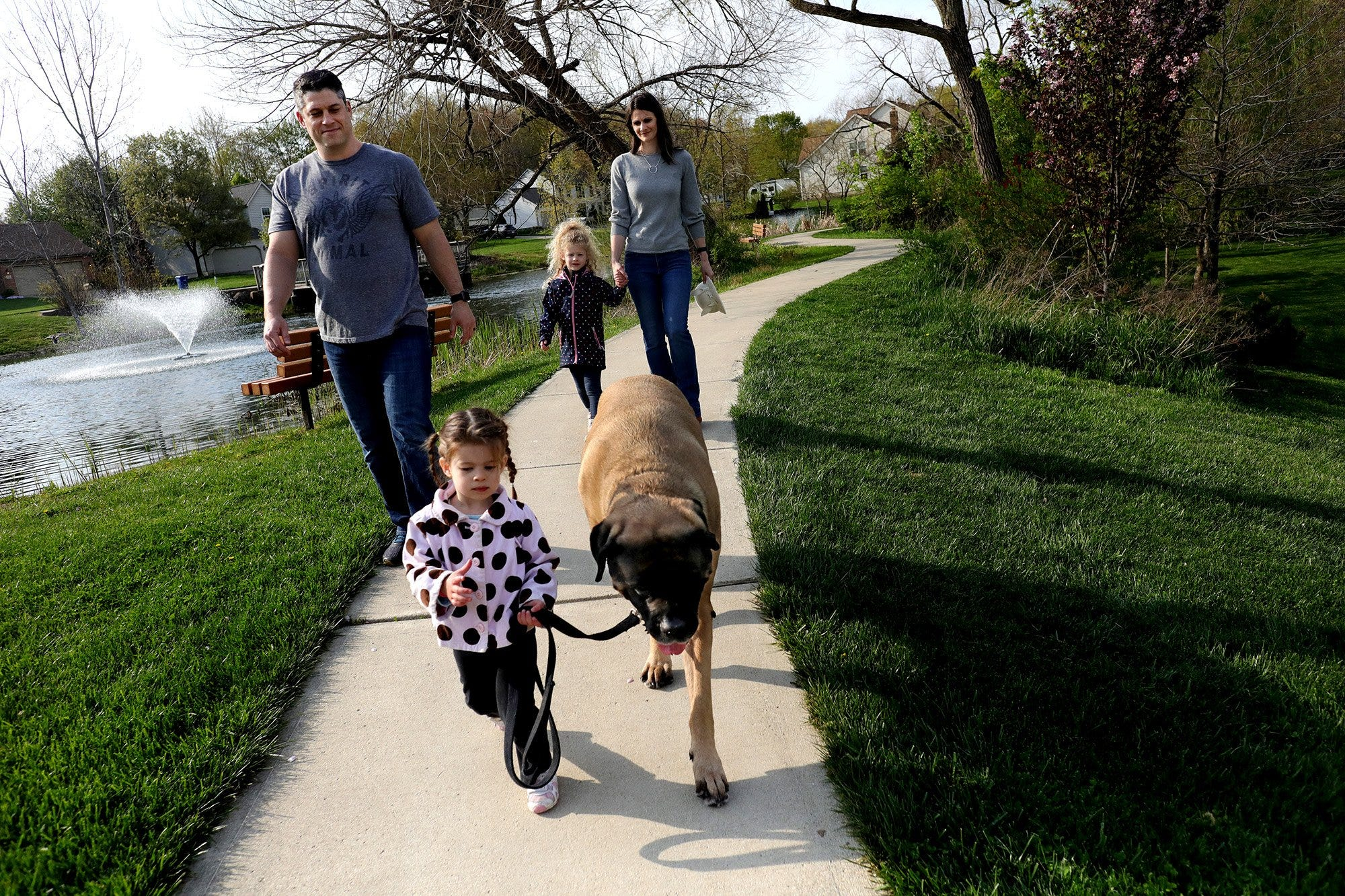 Leila, 2, leads the way with Bane, as the Korn family heads home during a walk in their Gahanna neighborhood before dinner.
