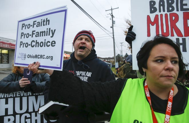 Clinic escort Michelle Davis (right) holds a sign in front of anti-abortion protester Michael Coughlin while he's speaking outside of Your Choice Healthcare of Columbus on Friday, Nov. 9, 2018. People gathered in protest of the clinic being blessed by a coalition of religious leaders. [Tyler Schank/Dispatch]