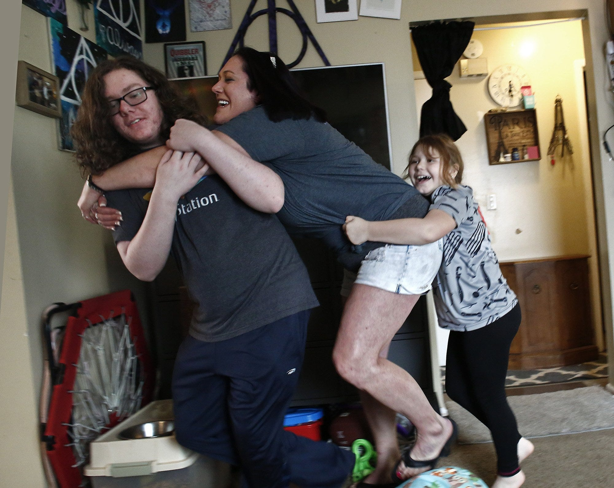 A group hug turns into a wrestling match between Sara Jucha, center; son, Kasey Burns, 15, left; and daughter Lily Jucha, 8, right on  April 8.