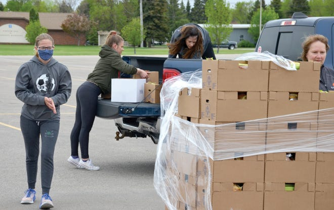 Volunteers put food boxes in a pickup at Crookston High School.