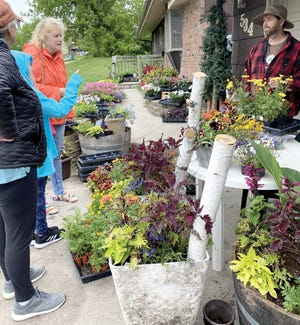 Shannon Stassen, right, helps customers at the flower and plant sale.