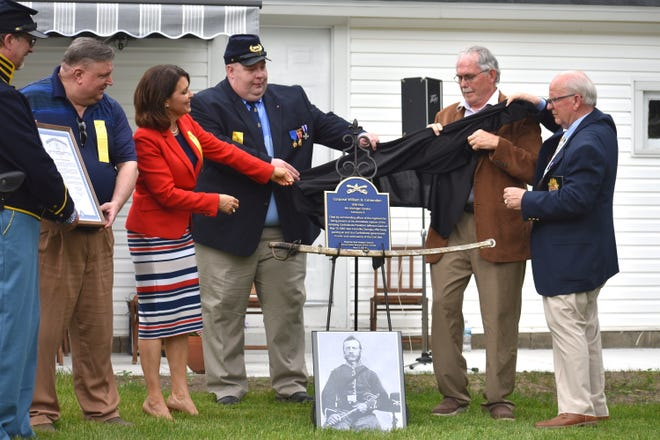 State Rep. Bronna Kahle, R-Adrian, along with Nathan Smith, the state commander of the Sons of Union Veterans of the Civil War; Tracy Oberleiter, a staff member of Sen. Dale Zorn, R-Ida; and Gary Naugle, president of the Tecumseh Area Historical Society, unveil a memorial Sunday afternoon to William H. Crittenden, a corporal in Company E of the Michigan 4th Calvary, who was responsible for the capture of Confederate President Jefferson Davis during the Civil War. Crittenden is a Lenawee County native.