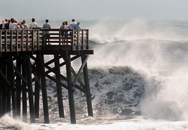 Spectators at the end of the pier in Flagler Beach on Aug. 29, 1999, as high tide and huge waves generated by Hurricane Dennis pounded the Florida coastline.