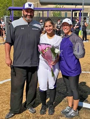 Wallenpaupack Area senior Kayla Schmalzle was recently lauded for her four seasons with the Lady Lady Bucks softball program. Sharing her celebratory moment are her parents Todd and Lori Schmalzle.