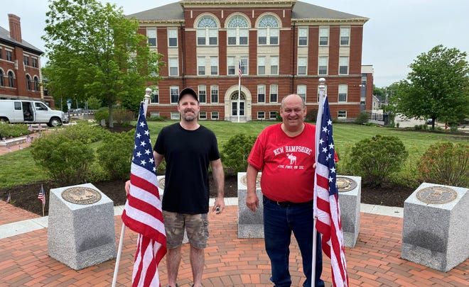 Brian Jacobsen of Immanuel Insurance Agency, left, and Dover Mayor Robert Carrier put up American flags in Dover's Veterans Park Saturday.