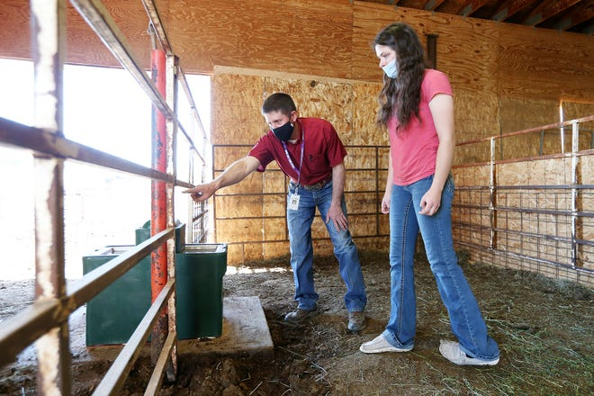 Cheyenne Central High School agriculture teacher Tommy Cress talks with junior Katey Carson, 16, about plans to weld a fence at the Clark Allen School Farm in Cheyenne, Wyo., on April 30, 2021. The farm provides hands-on agriculture education for area students. (Michael Cummo/The Wyoming Tribune Eagle via AP)