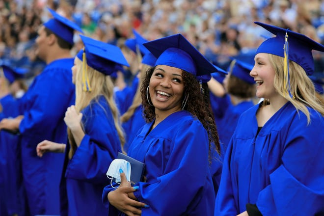 Hutchinson High School seniors Vanessa Clark, left and Hailey Compton laugh together at the end of their graduation ceremony Sunday afternoon at Gowans Stadium.  To see more photos from graduation, go to www.hutchnews.com