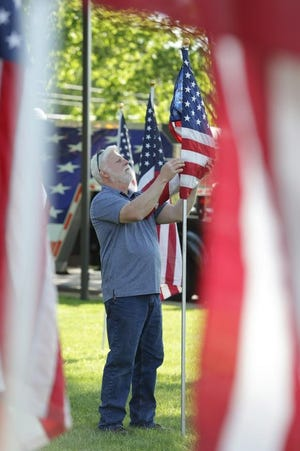 Steve Toohey, president of Operation: Flags of Freedom, unfolds a flag during a previous Memorial Day weekend display in Perry Township.