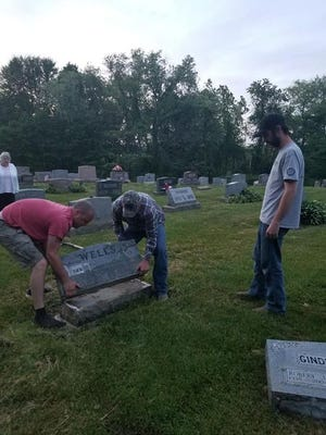 Volunteers clean up toppled headstones at Union Cemetery in Canal Fulton. On Friday, a driver veered off the roadway striking a trash can, a Canal Fulton city limit sign and several headstones in the cemetery before fleeing.