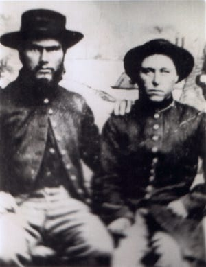 Jennie Hodgers, aka Albert Cashier, right, sits for a portrait with a bearded fellow soldier, whose identity is unknown, around the time of the Civil War.