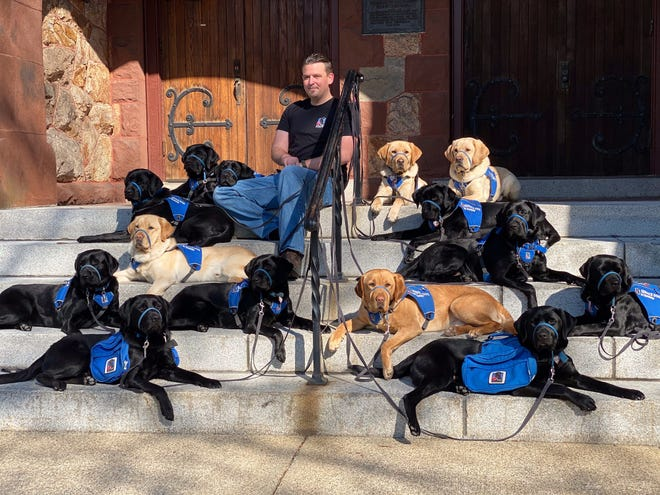 Tyler Gribi, NEADS' newest Trainer, with 14 NEADS Service Dogs in Training at the Gale Free Library in Holden April 20.