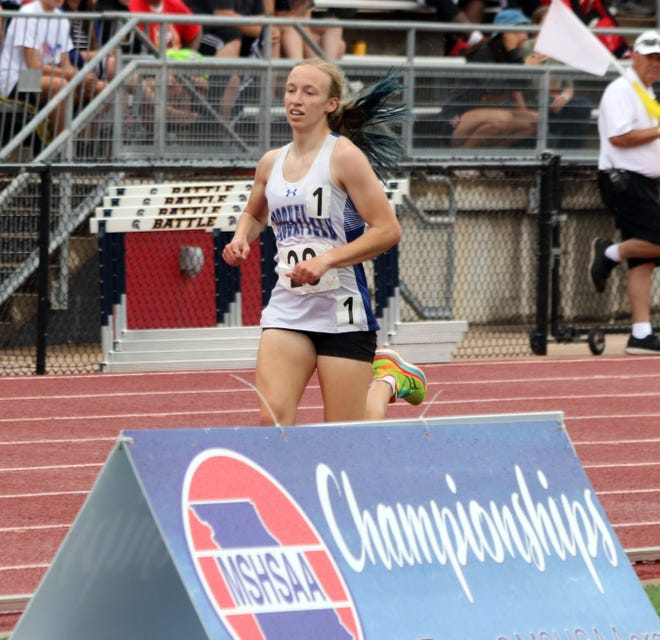 """Passing by a sign that denotes an event she says she considers """"home,"""" Brookfield High School junior Alexandra """"Alex"""" Sharp has the third-lap lead in the 1,600-meters run during the Missouri Class 2 girls' track-and-field championships at Jefferson City Friday, May 21. Sharp repeated as state champion of the race and also won three state medals, just as she did in 2019."""