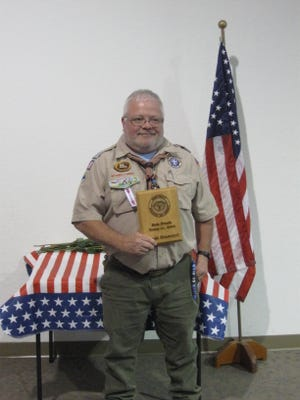 Rob Frock holding his District of Merit Award.