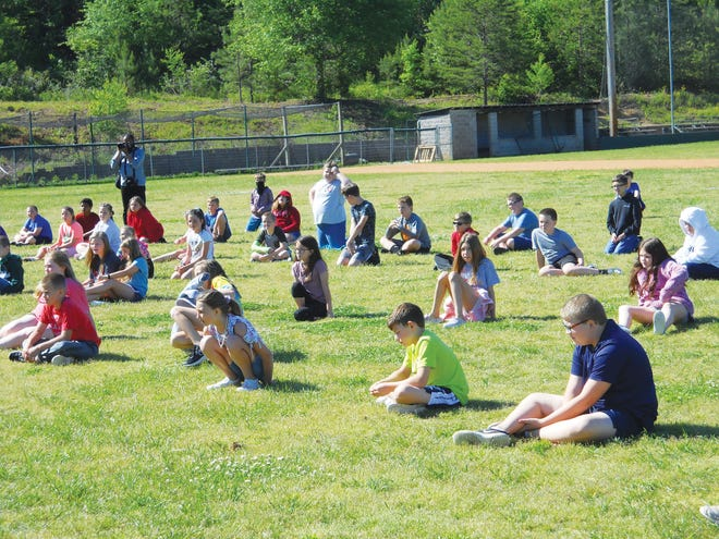 Children at Midway Elementary School sit outside on the athletic field to watch the science experiment on May 14, 2021.