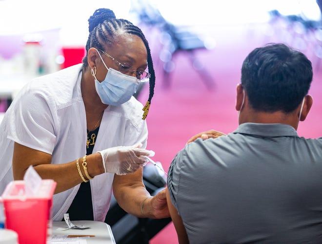 A nurse gives a patient a COVID-19 vaccine.