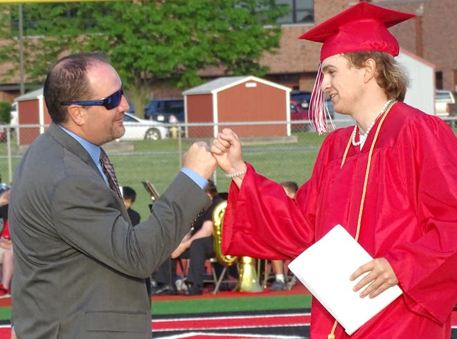 Ottawa High School senior Lane Altic receives a fist bump from Dr. Ryan Cobbs, the Ottawa superintendent and former OHS graduate.