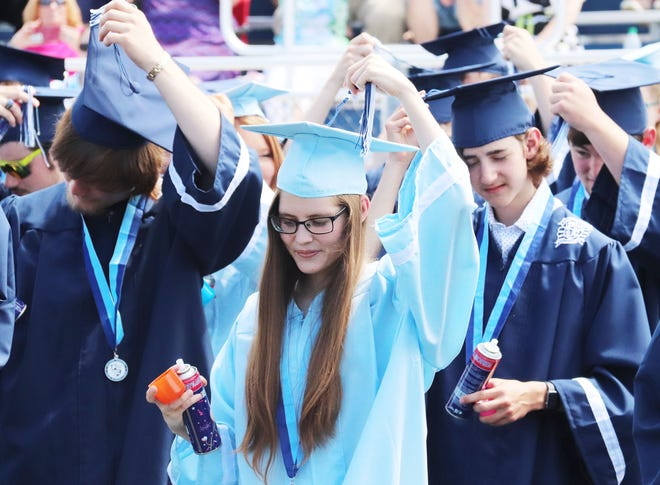 Abby Bergstralh joins her classmates in turning her tassel from the right to the left to signify their graduation from Prairie Central High School Saturday.