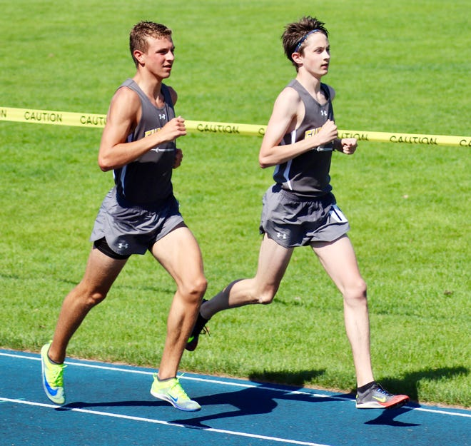 Sam Paga (left) and Hammond Law of Petoskey St. Michael Academy run during a race in the Division 4 regional in Indian River Saturday.