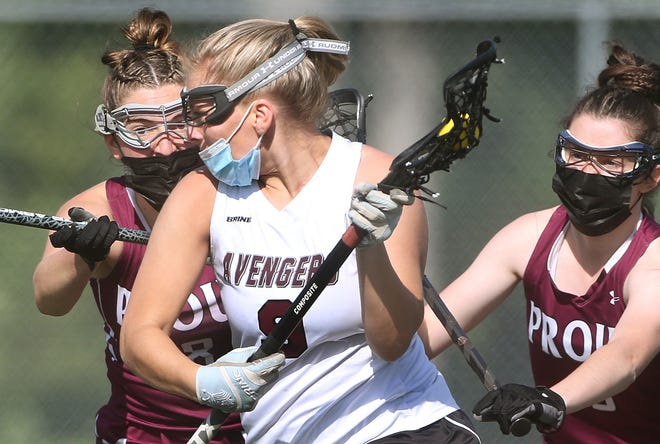 Abby Walsh possesses the ball for East Greenwich during a high-school lacrosse game against Prout on Monday. At left is Olivia Barber, and at right is Saoirse O'Connor.