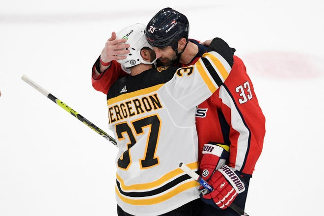 Boston Bruins center Patrice Bergeron (left) and Washington Capitals defenseman Zdeno Chara hug after Game 5 of an NHL hockey Stanley Cup first-round playoff series on May 23, 2021 in Washington. The Bruins won 3-1.