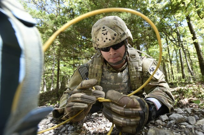 Sgt. Jorge Morales, a bridge crewmember with the 35th Engineer Battalion, ties a branch line from a shaped charge May 13 at Range 33 as part of the hasty road crater emplacement mission during the Combat Engineer Skills Division's first permanent-party field-training exercise May 10 through 14. Photo by Brian Hill