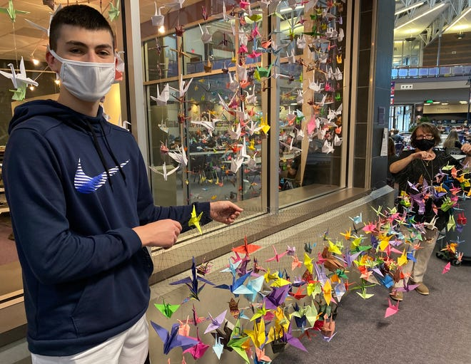 Jack Walter, a freshman at Jackson High School, displays paper crane artwork while Kim Germano, who teaches world history, holds the other end. Inspired by a Japanese girl who died of leukemia in the aftermath of the atomic bombing of Hiroshima in World War II, the crane project combined curriculum in art, history and theater.