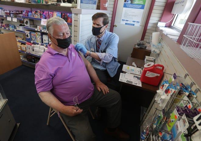The Medicine Center pharmacist Mark Giangardella gives Thomas Beppler the COVID-19 vaccine.