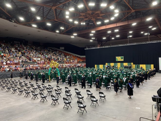 The graduating class of 2021 stands at Sunday's ceremony to the applause of all in attendance.