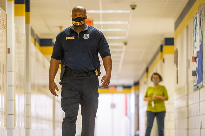 Anthony Pearson, a resource officer at Riley High School in South Bend, walks the hallways on Friday.