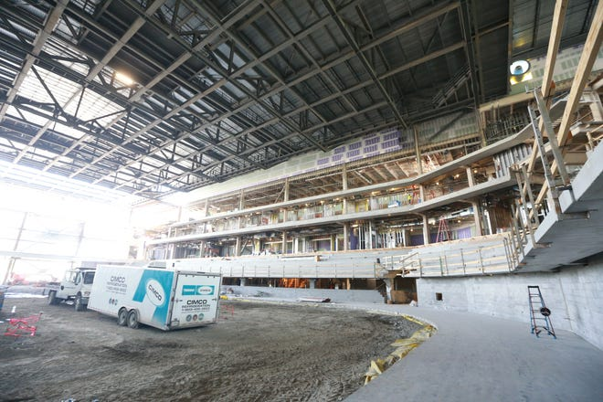 Concrete has been poured around the outside of what will be the ice rink on the arena floor.