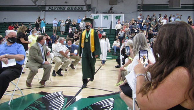 Valedictorian Ben Smith is captured on smartphones as he makes his way through the socially distanced and masked crowd to the stage where he and his classmates received their diplomas. [Photo by Dave Clarke]