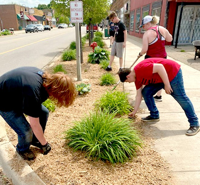 Sam Marshall, Johnathan Hire and Taylee Allison, members of Mendon High School's National Honor Society, tidy-up downtown May 21 at the school's annual NHS volunteer day. Partly visible in the background is Eric Hessling.
